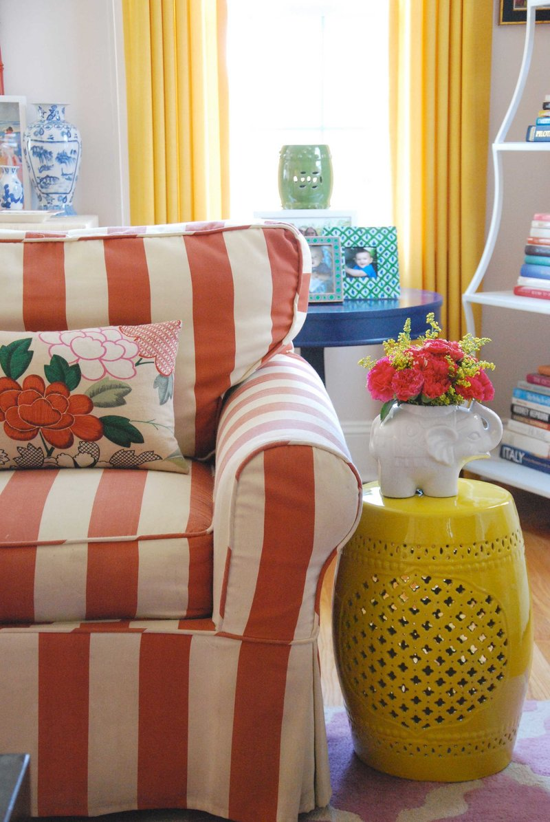 An orange and cream striped chair next to a yellow end table with an elephant vase.