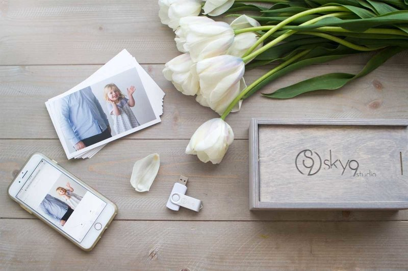 Sky 9 Studio | Digital files for purchase at East Bay family photography studio; image is of USB with digital files, mobile phone app, photo proof box and white tulips on a wooden table