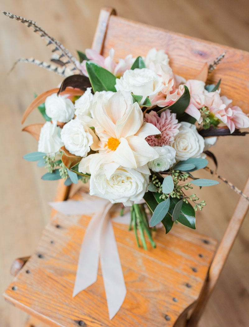 Bohemian bridal bouquet with feathers sitting in a chair