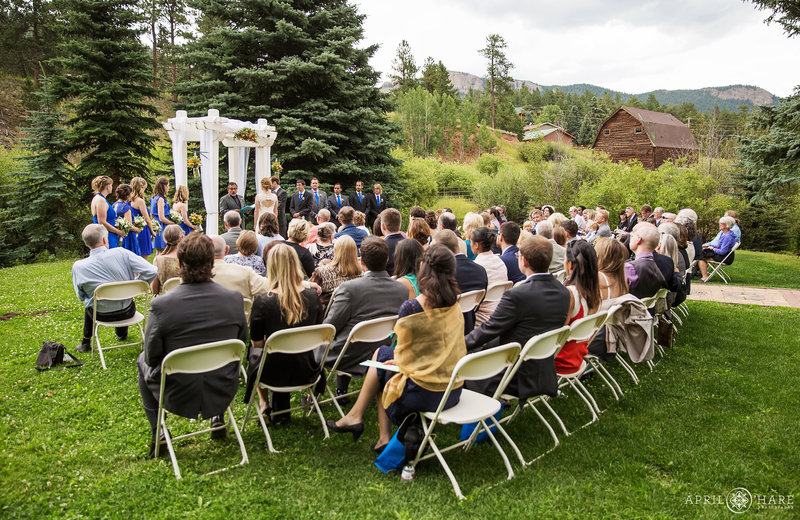 Wedding ceremony in Colorado Mountain Meadow with Barn in Distance