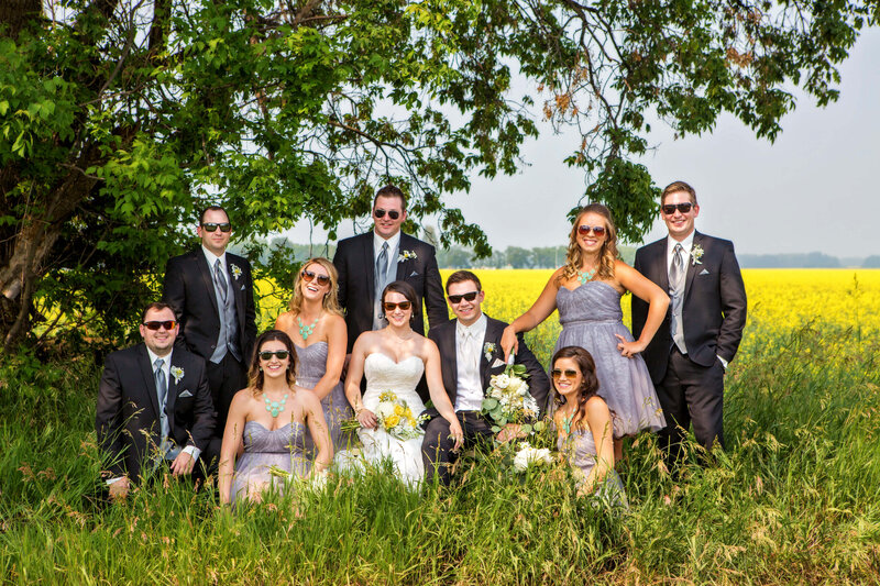 large wedding party wearing sunglasses  sitting in tall  grass
