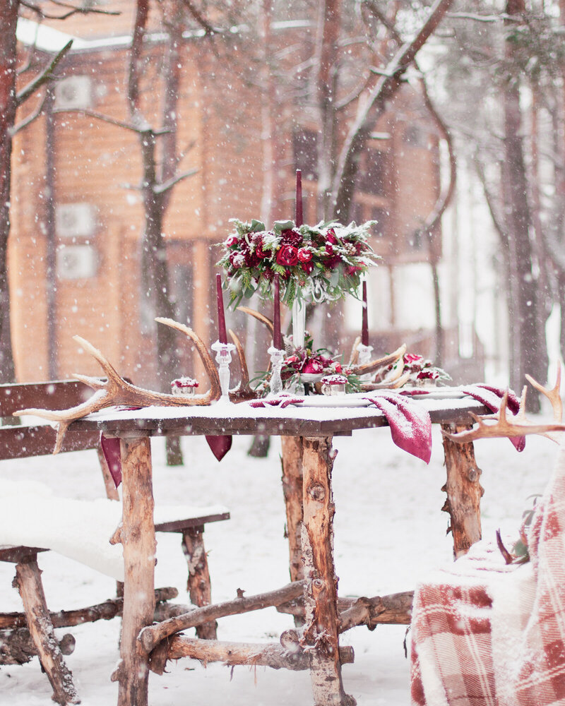 Table made of pine in snowy forest in winter with red wedding table setting for a proposal or event. Winter wedding decor.