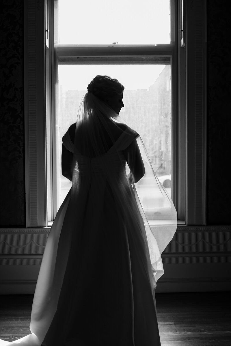 Silhouette of bride standing in a window at the Watson Curtze Museum in Erie PA