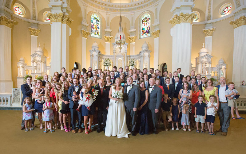 Bride and groom pose with bride's family at St. Patrick's Church wedding