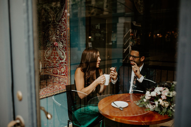 Couple sharing a drink at a coffee shop during their engagement session