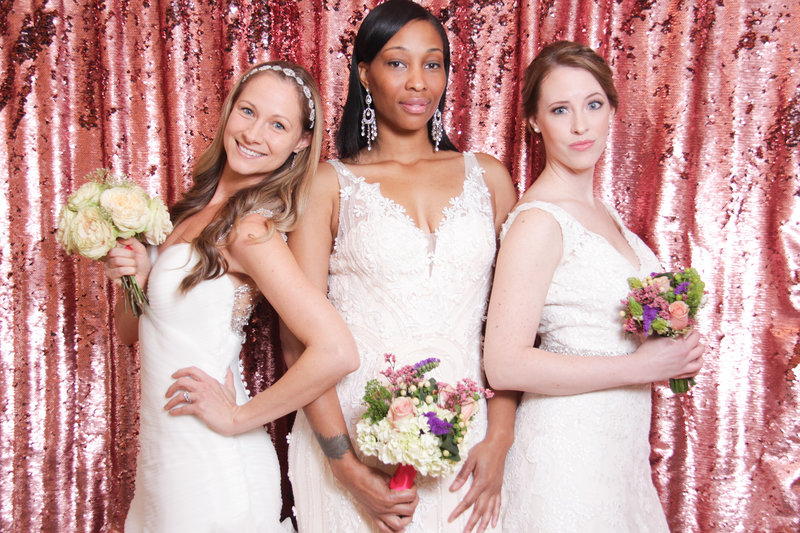 threee beautiful brides displaying gorgeous dresses on a gorgeous rose backdrop