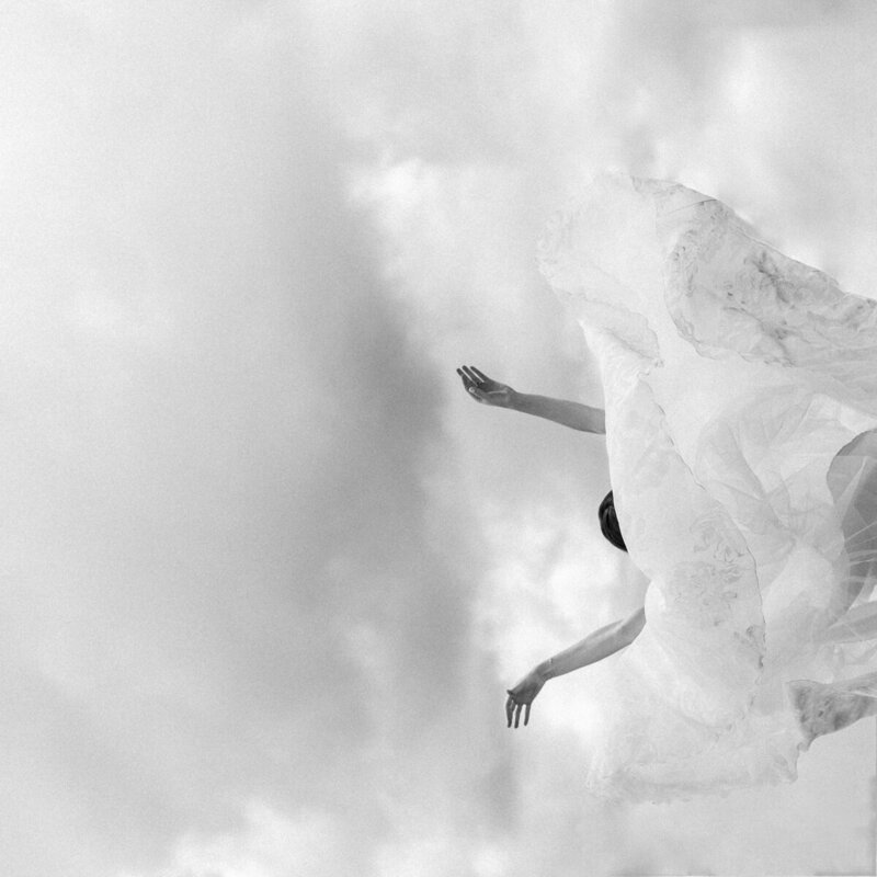 Black and white off beat wedding photo of a bride thowing her gown over her head to seem like she is floating in the clouds or falling from the sky.