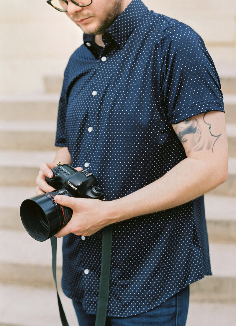 Man in navy polka dot shirt holding camera with tattoos on arm