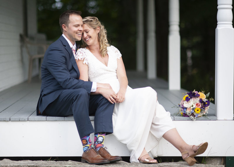 Bride & groom smile & lounge together on the front porch at their wedding in Gorham, Maine