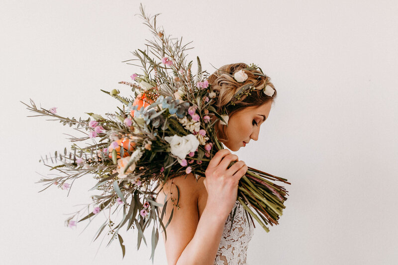 bride holding large bouquet of flowers over shoulder