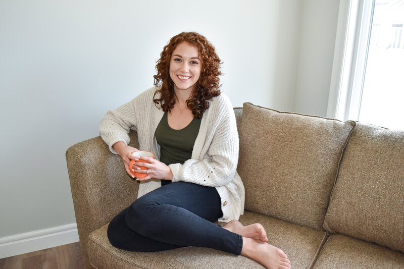 A woman who is a Showit website designer with curly red hair sitting on a brown couch holding an orange mug smiling at the camera