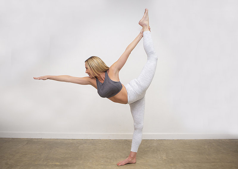 Yoga teacher Nicole Duke smiles & holds standing bow pose at Hotsource Yoga in Aptos