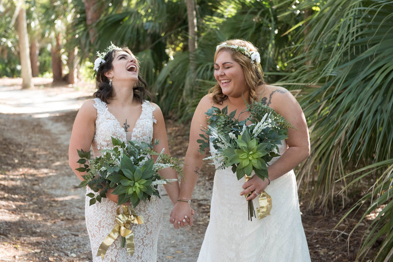 Two brides holding hands and carrying succulent bouquets in wooded area
