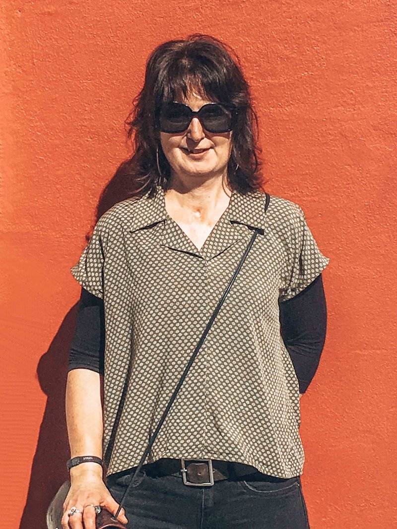 Lynda standing in front of red wall in Dunedin, New Zealand in home sewn shirt.