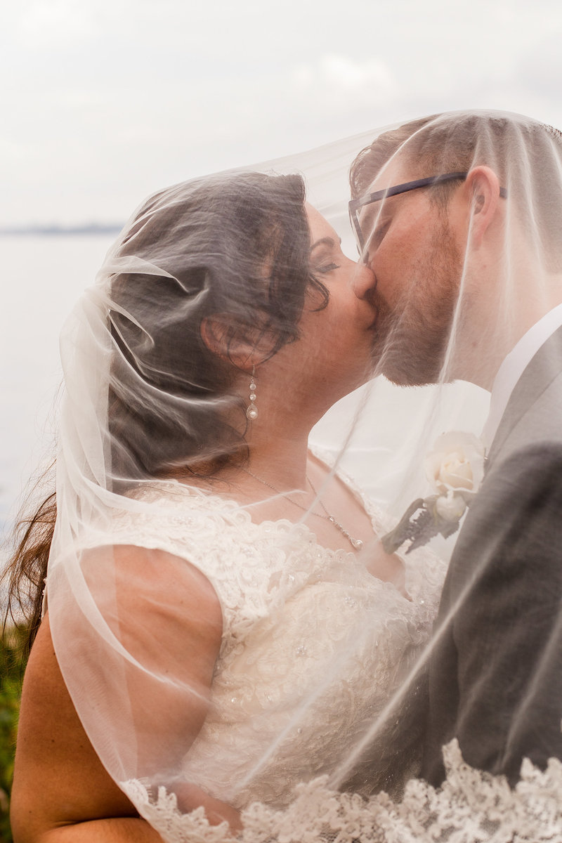 Bride and groom kiss under bride's veil along Lake Erie