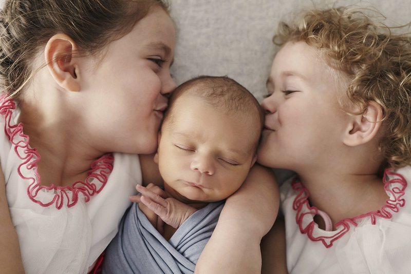 Sister's kissing their newborn sleeping brother
