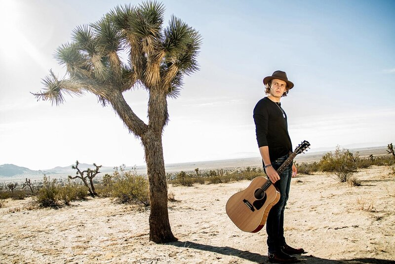 Musician photo Cole Bradley standing in desert by Joshua Tree holding acoustic guitar