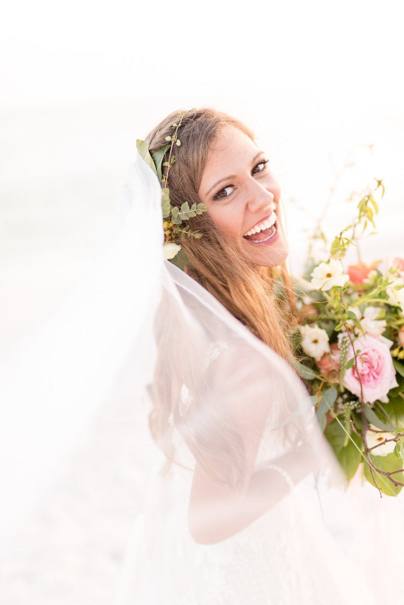 Bride laughs towards camera at sunset.