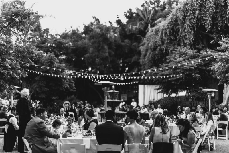Bride and groom enjoy their wedding reception surrounded by loved ones outdoors under twinkle lights