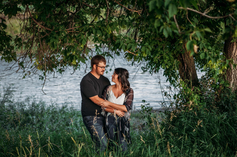 engaged couple embracing under a tree with river behind