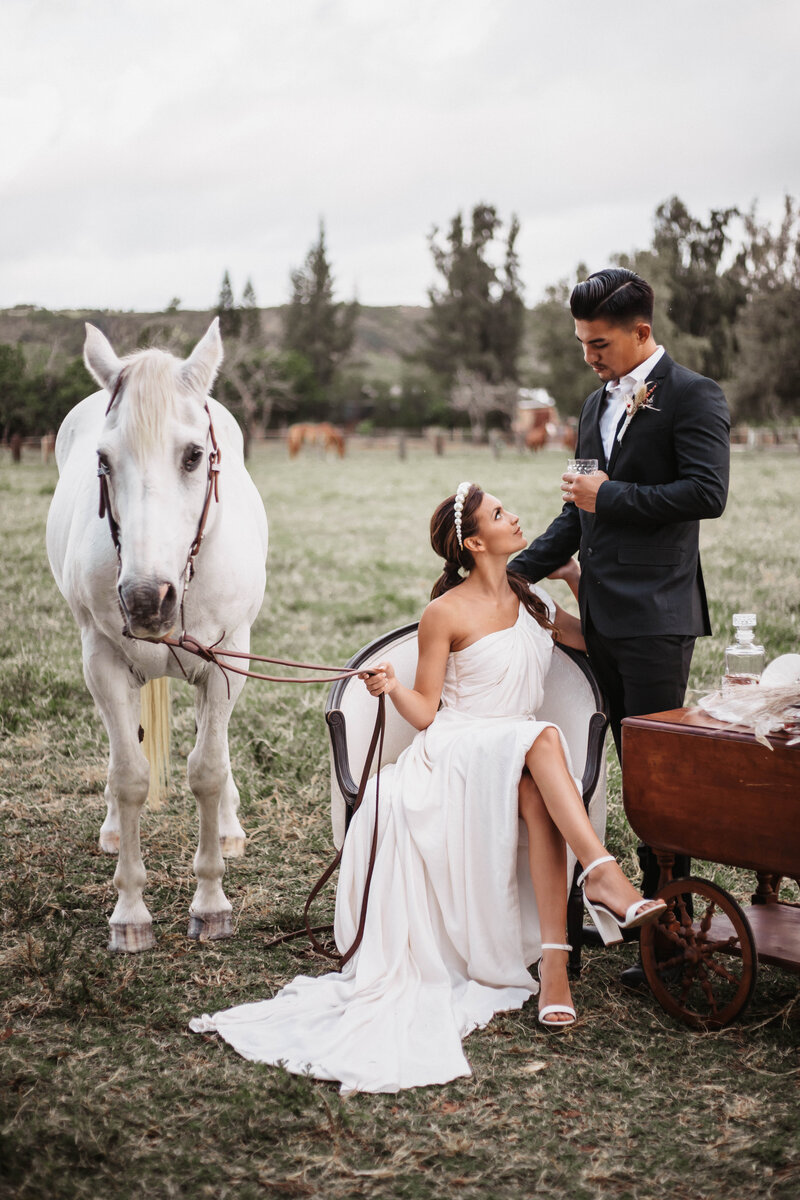 Oahu-kawailoa-horse-ranch-couple-poses-with-horse-during-hawaii-wedding-photographer