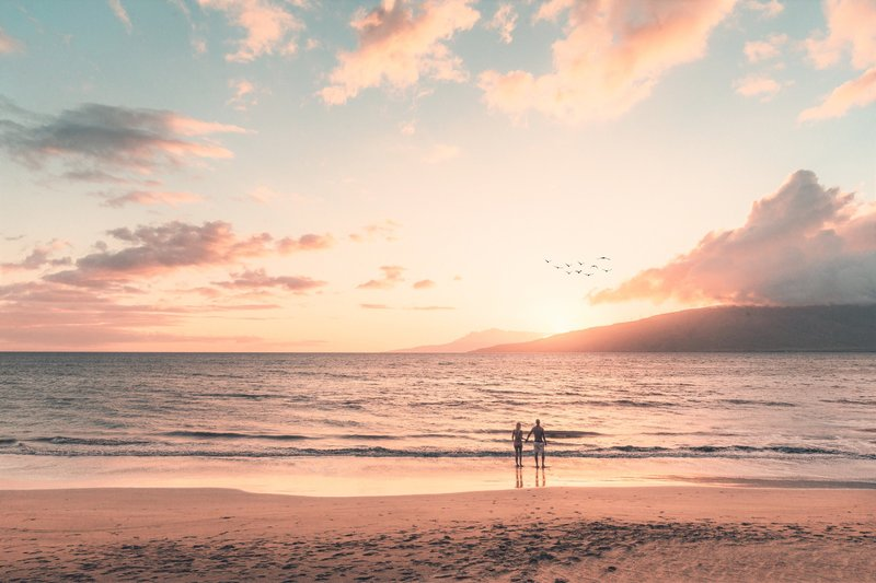 Couple watching a Maui sunset from the beach