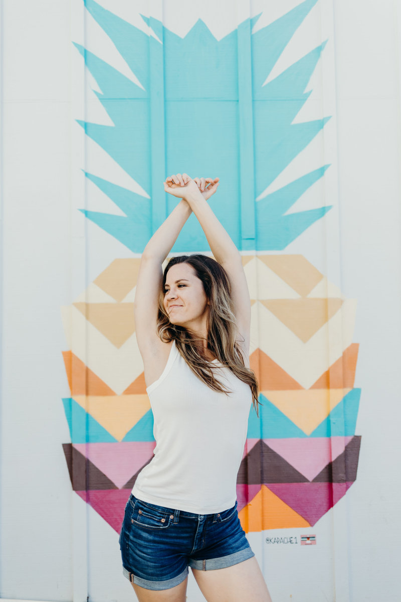 woman standing next to colorful wall with arms over head