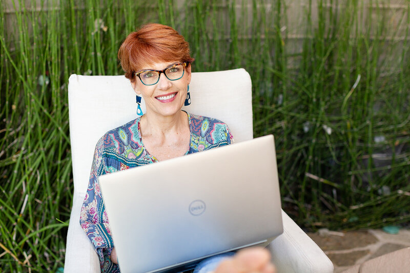Melissa offers private interior design coaching, holding her laptop and smiling