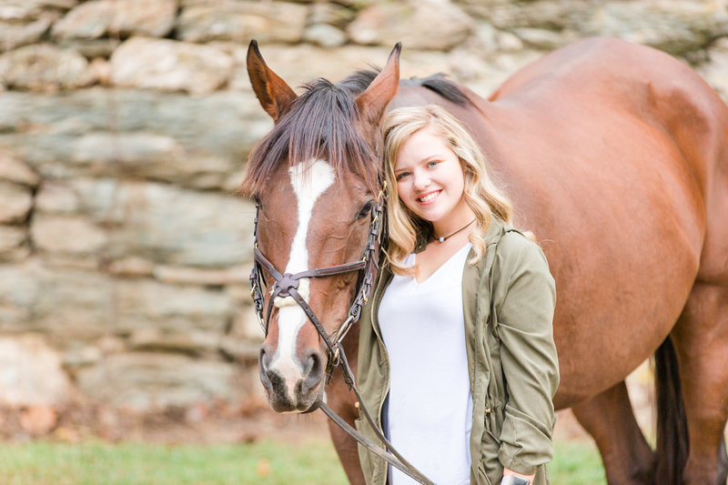 High school senior girl smiles for photo with her beautiful horse outside