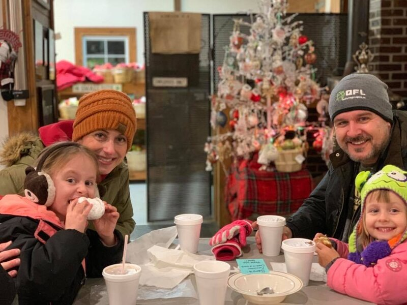 family enjoying hot apple cider and donuts