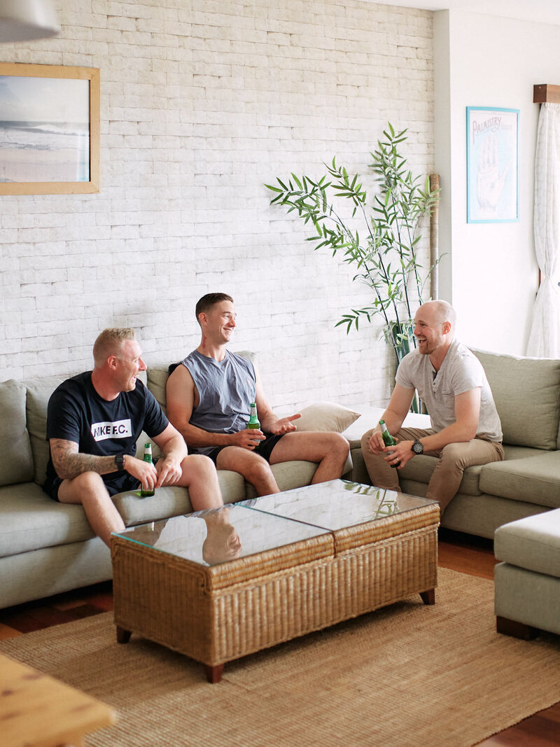 Three groomsman sitting on couch laughing with beers