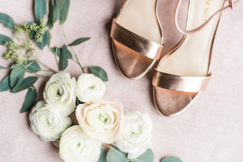 Elegant high heels placed on a pink canvas  with white roses.
