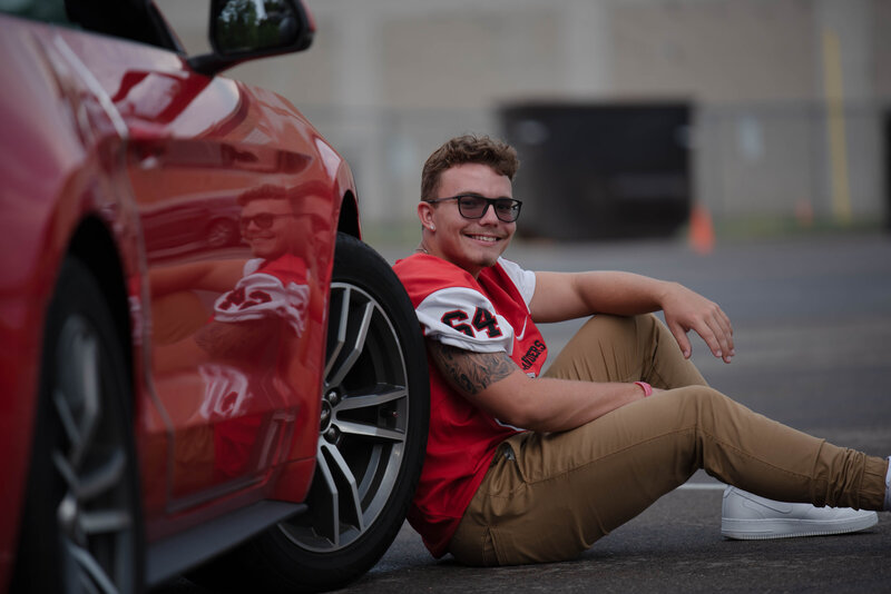 senior boy leaning against sports car
