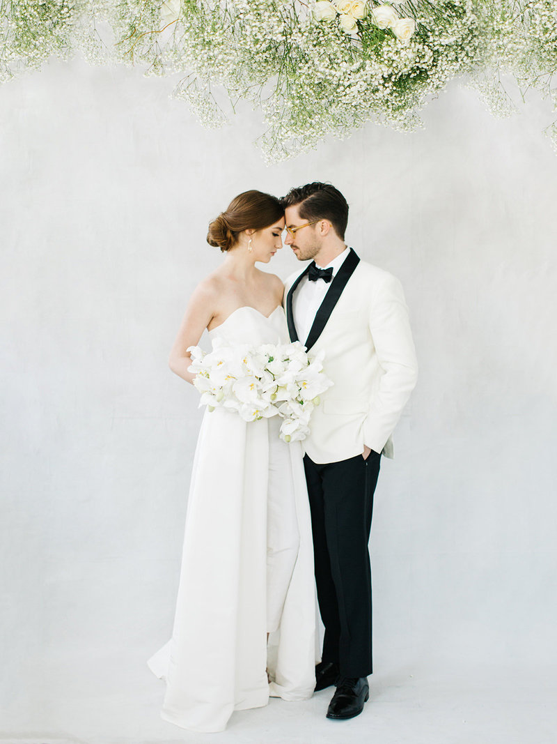 A destination wedding couple in wedding dress jumpsuit with  removable cape and dinner jacket