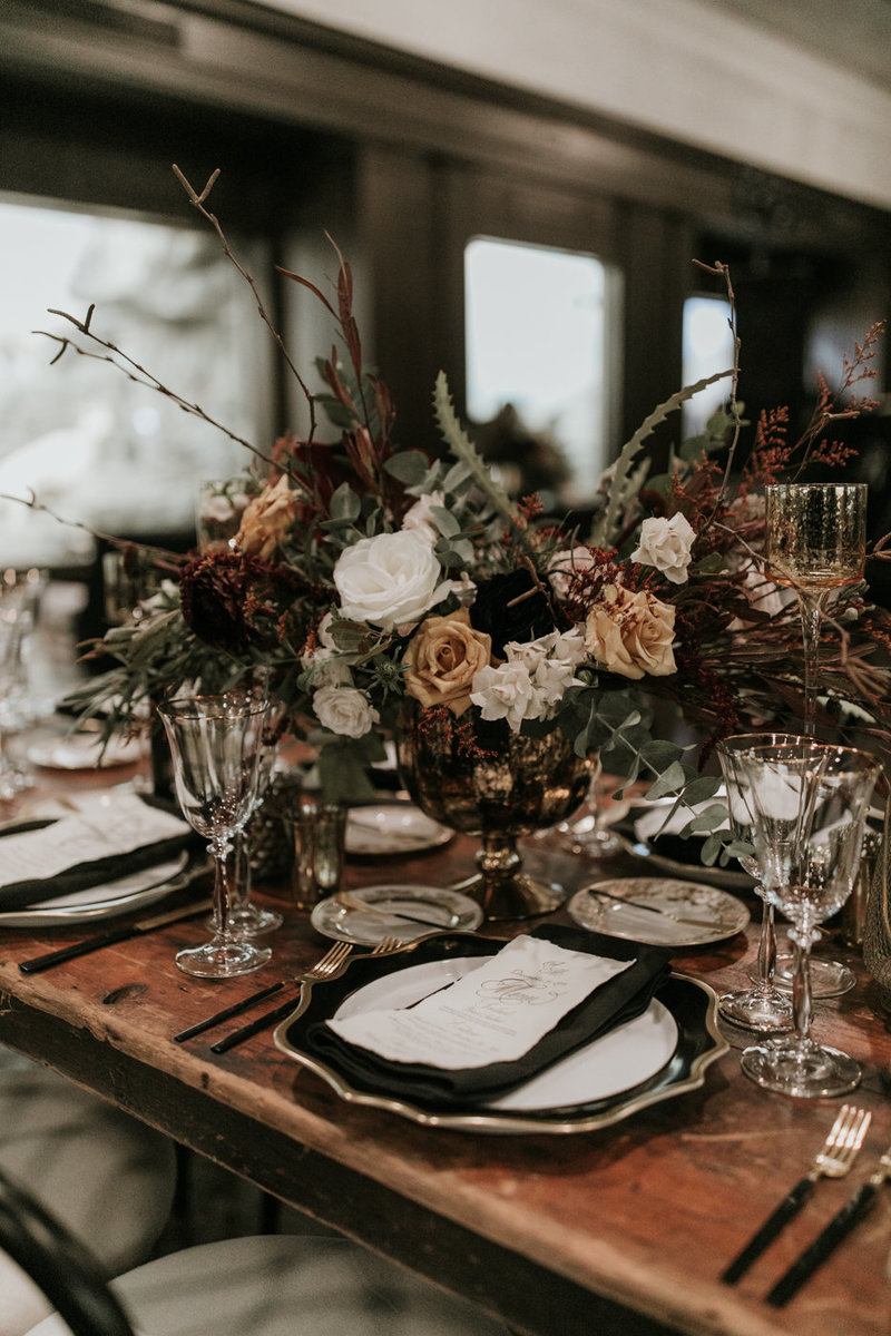 Wedding reception table setting at Natural History Museum with mood black plates and cutlery and dramatic floral centerpieces at this New Years Eve wedding