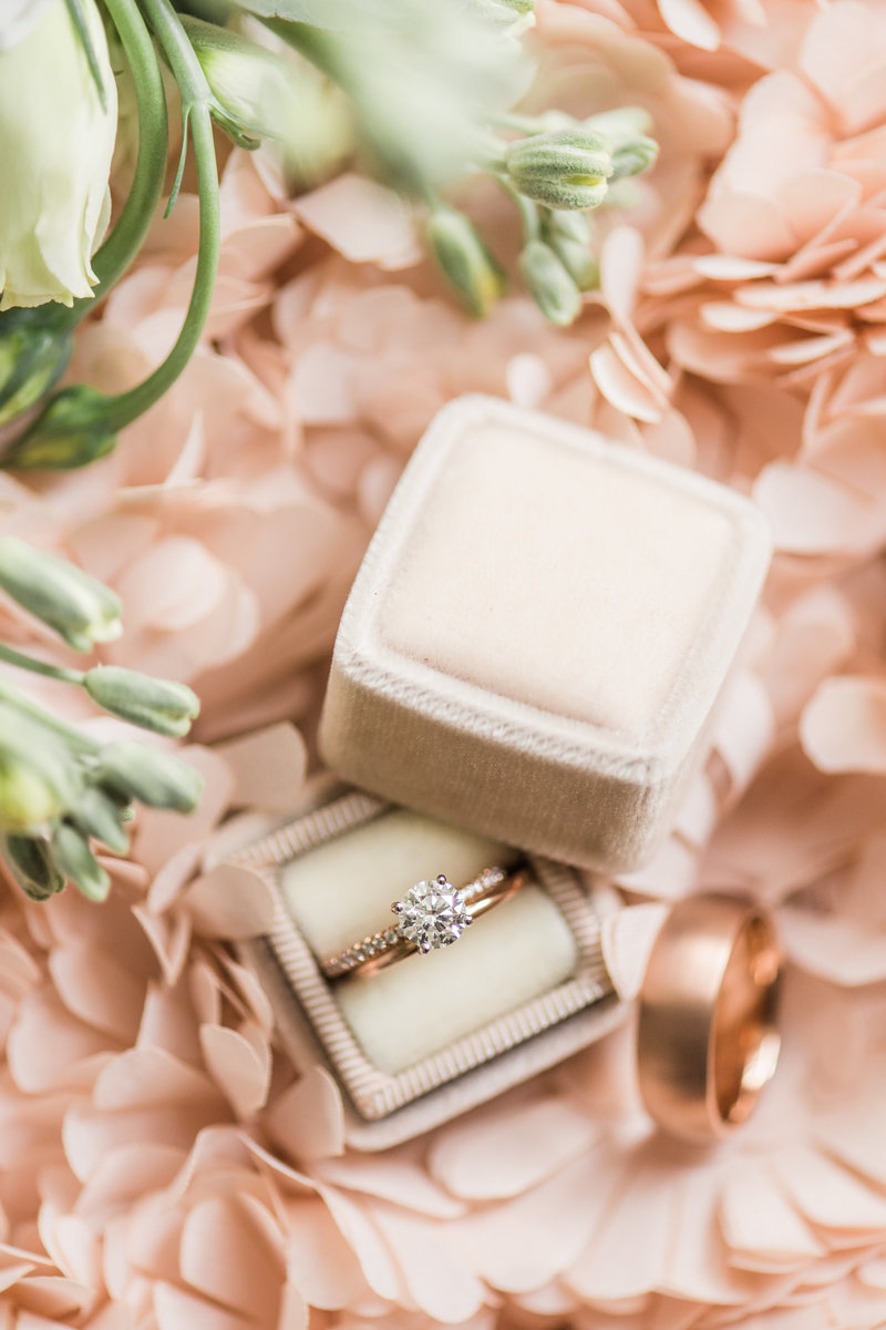 Rose Gold engagement ring placed in a Mrs. Box with pink ruffles in the background.