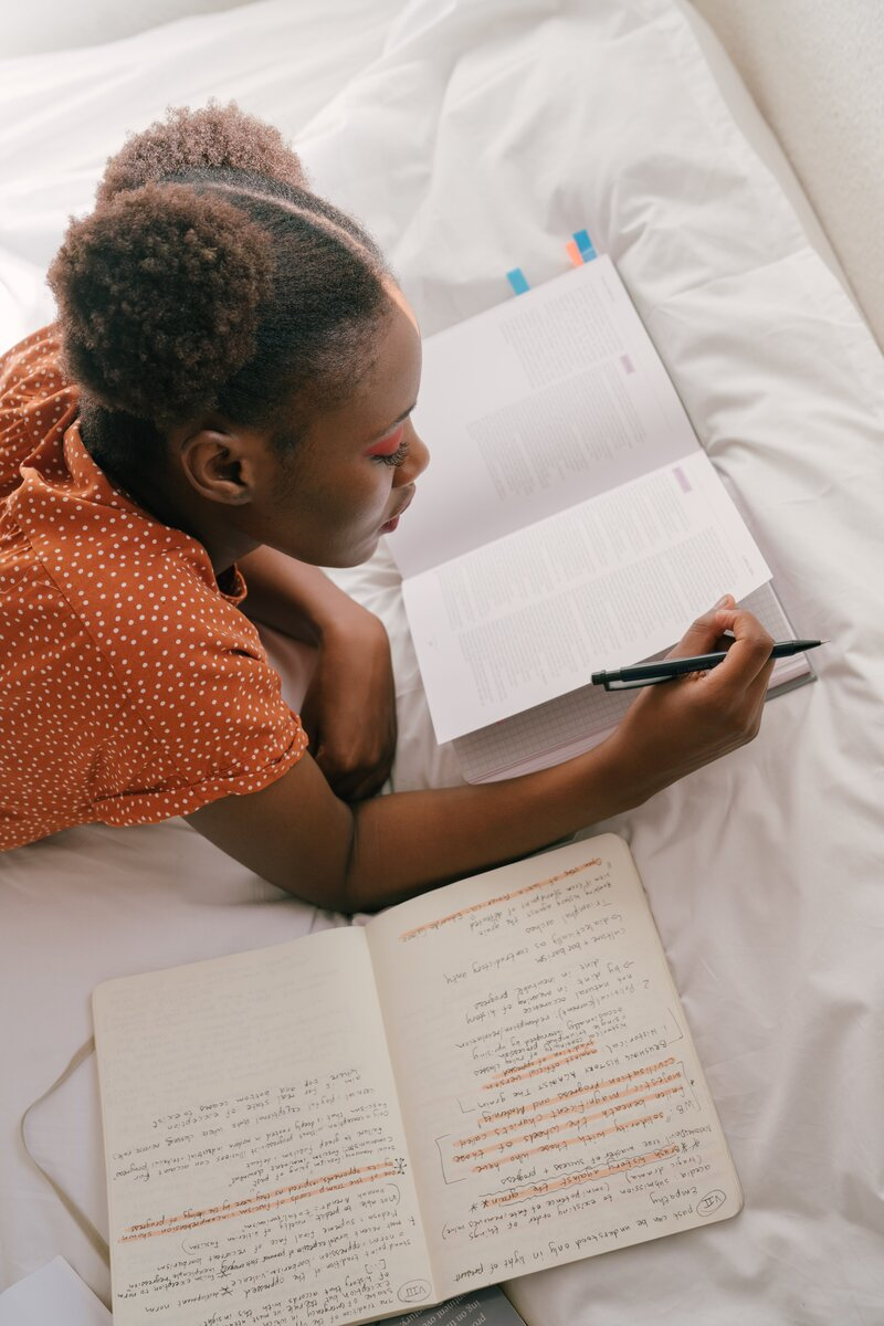 A Black woman laying on a bed reading a book