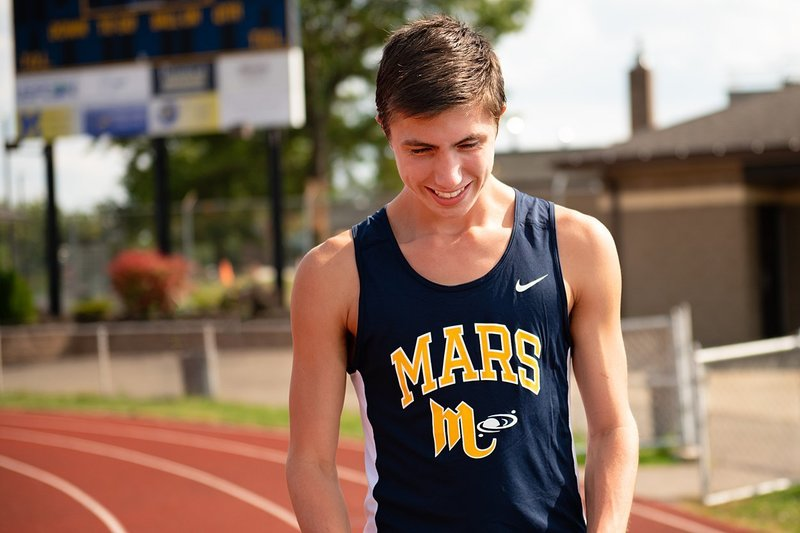 High school senior boy in Mars track uniform standing on track at Mars High School in PA