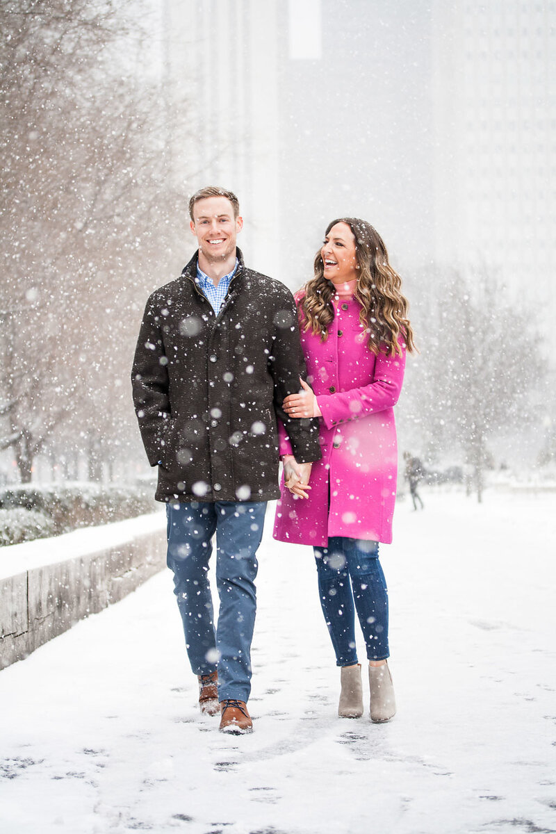 couple walk in the snow during snowy winter engagement session in Millennium Park Chicago