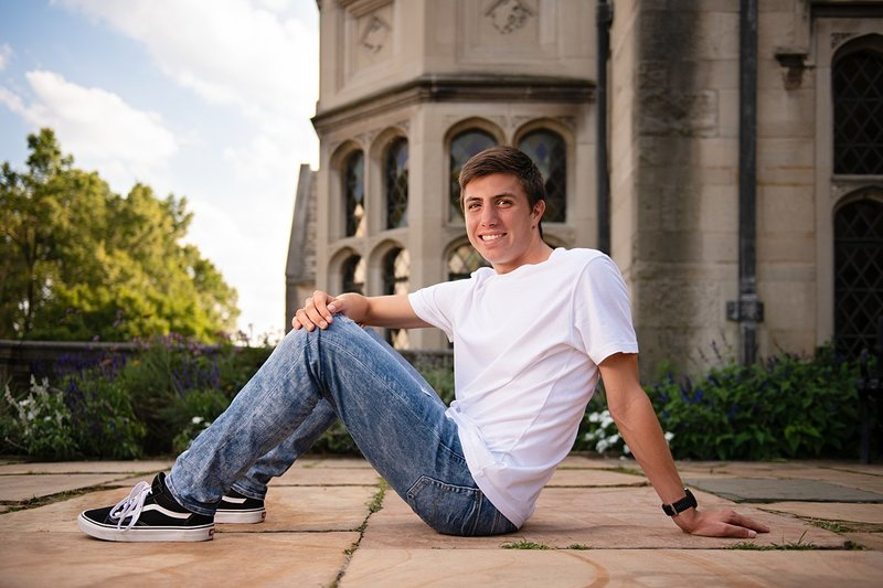 High school senior boy seated on stone plaza in front of Hartwood Acres mansion in Pittsburgh, PA