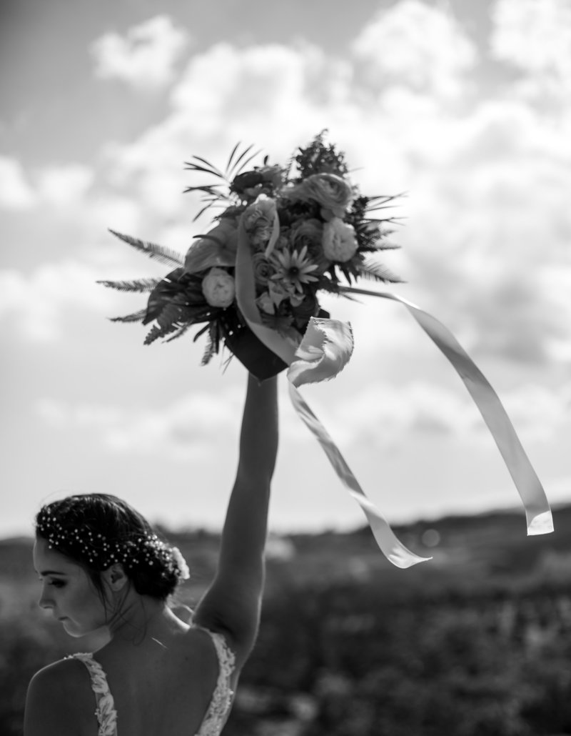 Black and white image of bride throwing wedding bouquet