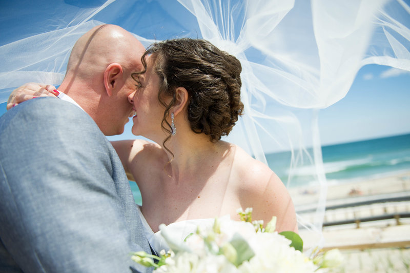 bride and groom laugh under veil at beach