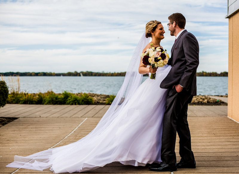 Groom pulls his bride close to him outside the Sheraton Erie Bayfront Hotel