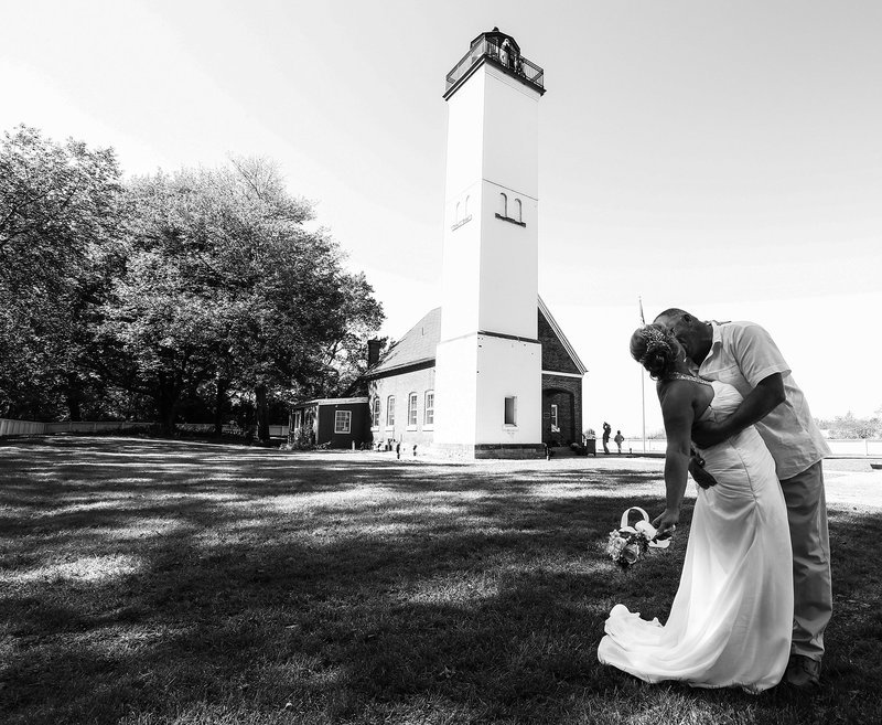 Bride and groom kissing  in front of lighthouse on Presque Isle State Park