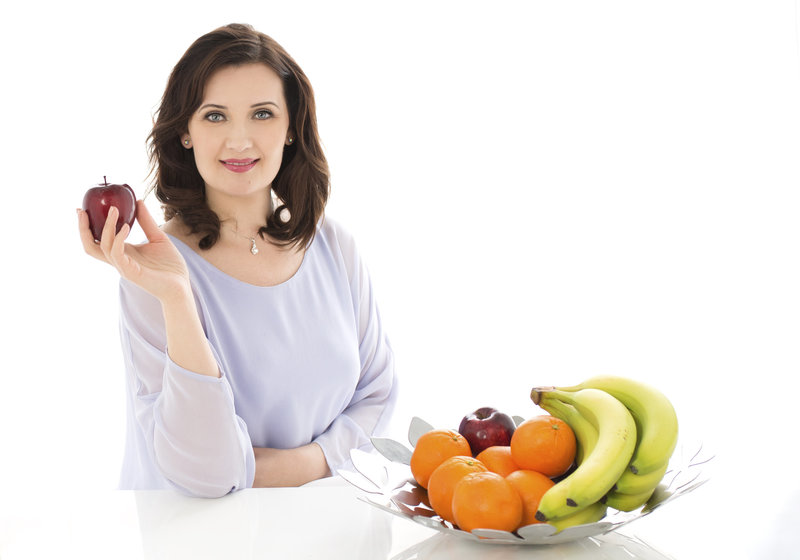 health and  nutrition coach sitting with apple in hand on desh looking beautiful and  confident with glowing skin chesnut color hair and  peral earings . basket of fruits kept o the desk . professional headhot of  confident woman professional