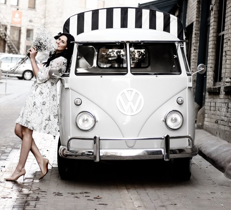 A gorgeous headon shot of a woman holding a bouquet of baby's breath leaning against a vintage VW pickup truck