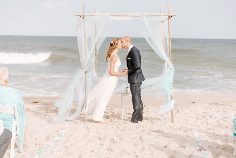 bride and groom share their first kiss during beach wedding