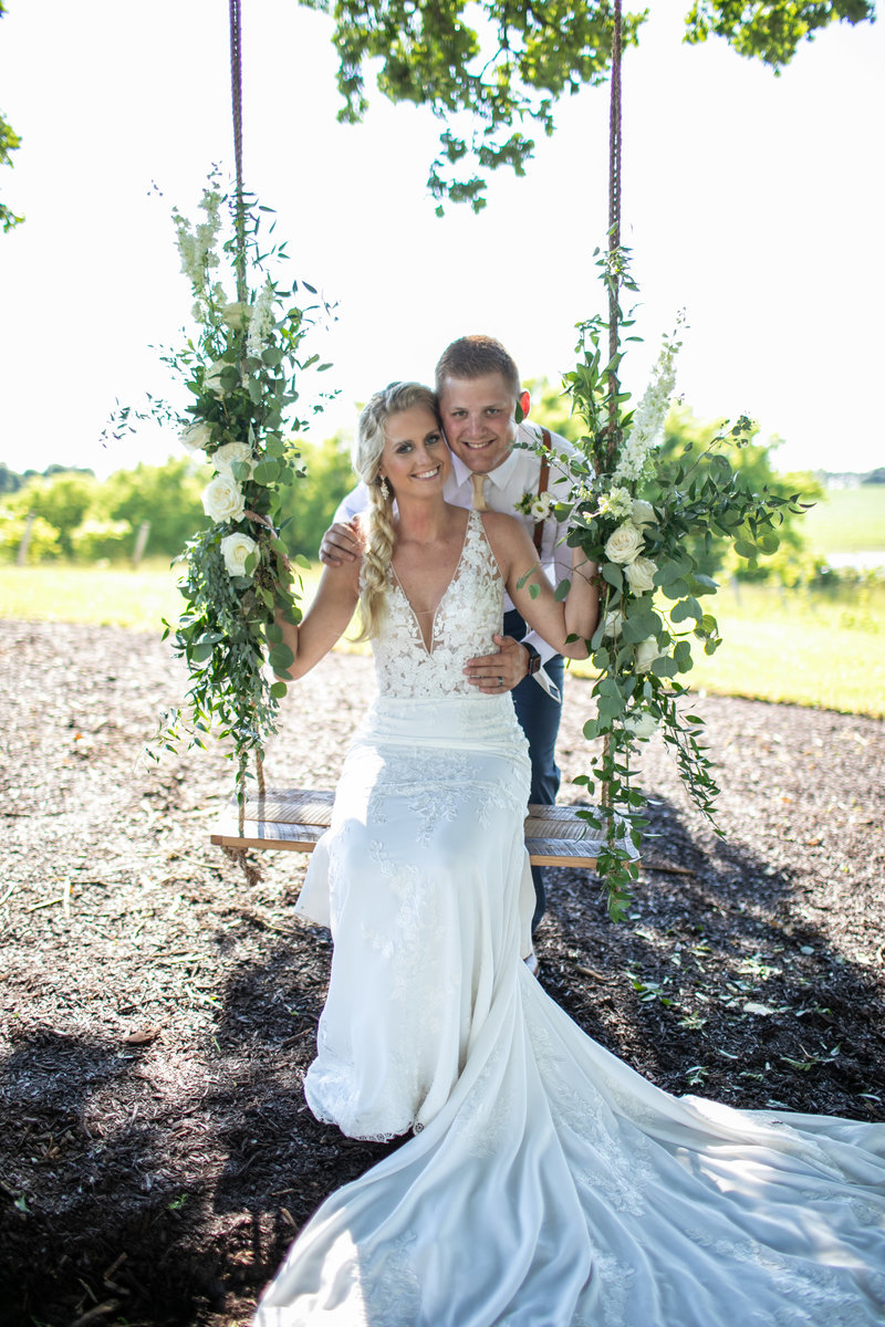 Bride sits on a swing adorned with floral arrangements while groom embraces her at Providence Vineyard in Hebron