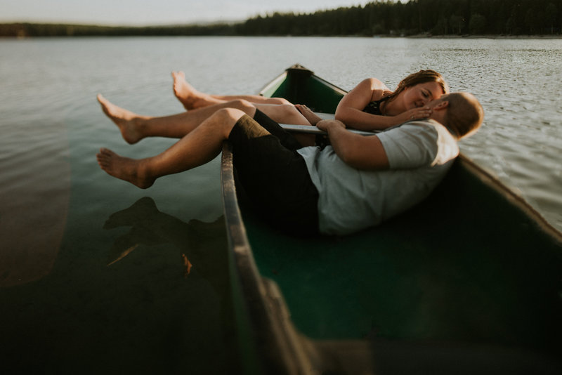 Kalispell MT Engagement Couple Cuddling in Canoe on Lake