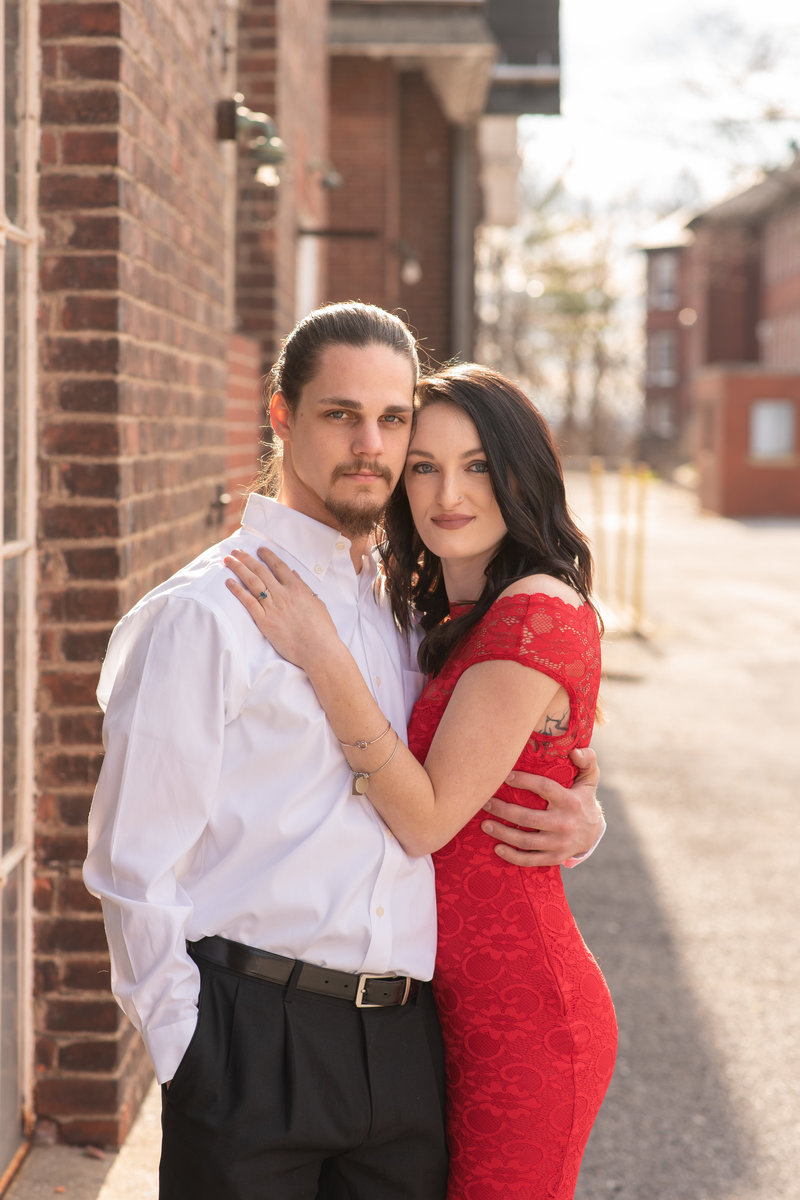 Engaged couple in dressy attire with brick buildings around them